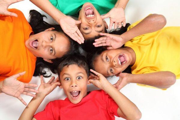 ילדים מחייכים עם חולצות צבעוניות מודפסות